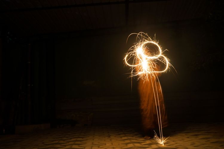 Person spinning illuminated sparkler while standing on footpath at night