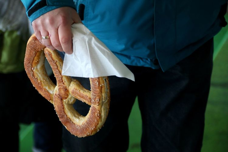 Midsection of person holding pretzel