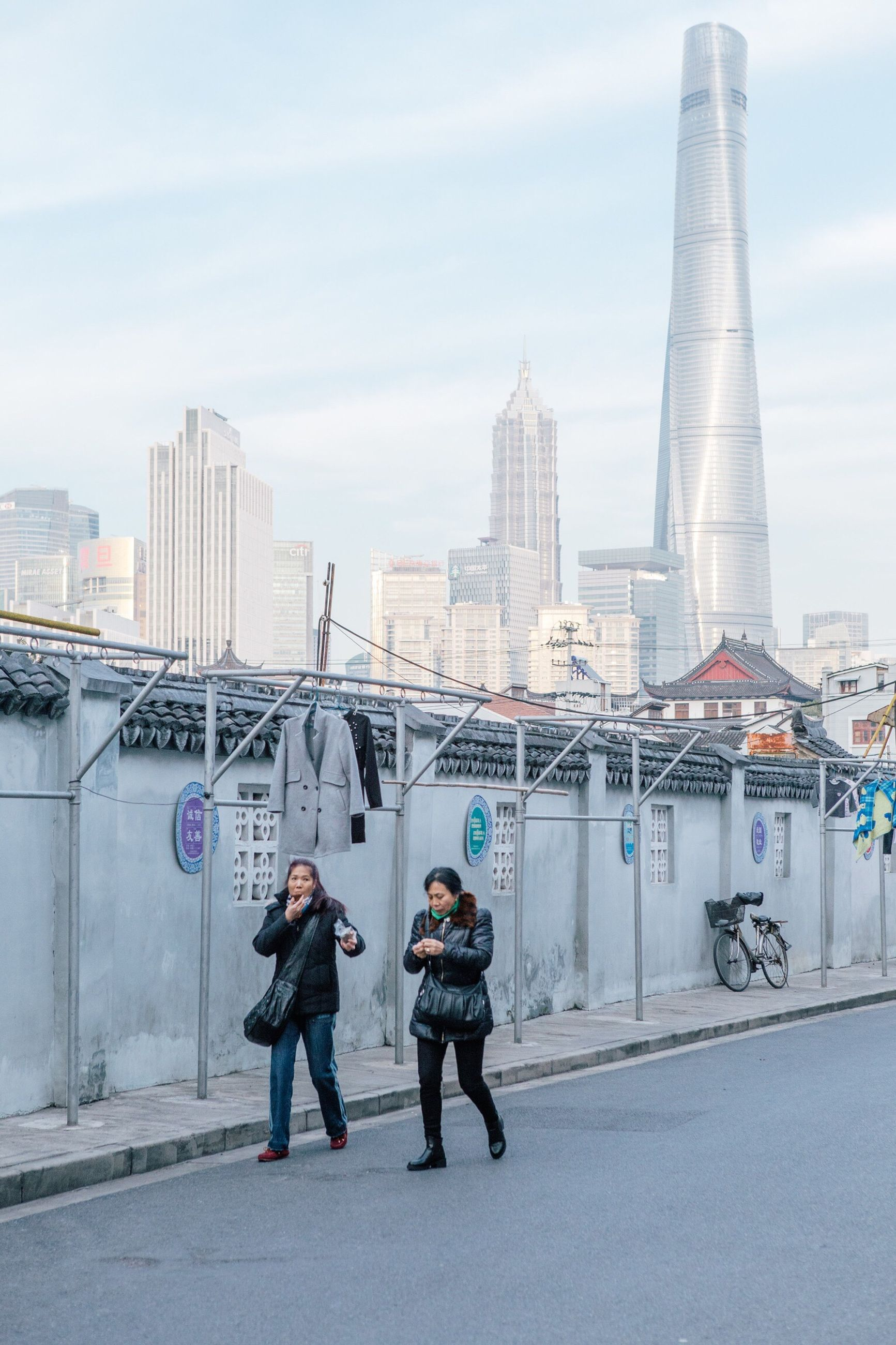 architecture, built structure, building exterior, city, full length, men, lifestyles, leisure activity, person, rear view, skyscraper, tower, sky, bridge - man made structure, casual clothing, city life, togetherness, day, suspension bridge, outdoors, tall - high, tourism, famous place