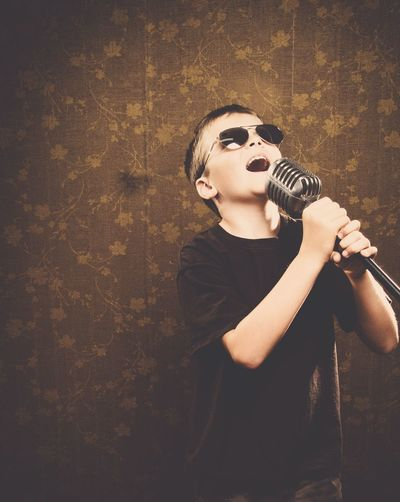 Boy Wearing Sunglasses While Singing With Microphone At Home