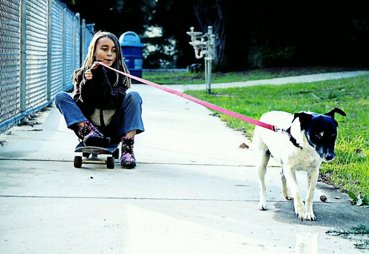 Girl Sitting On Skateboard While Holding Leash Of Dog At Footpath