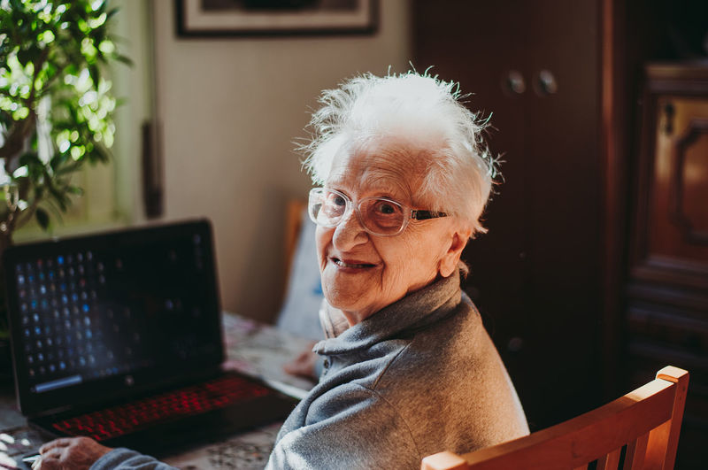 Portrait of smiling senior woman using laptop while sitting at home