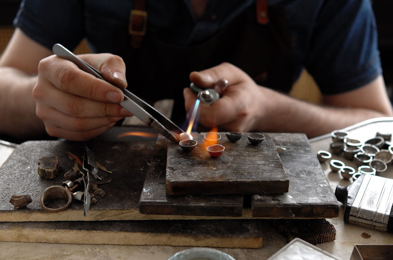Midsection of person working on jewellery workshop
