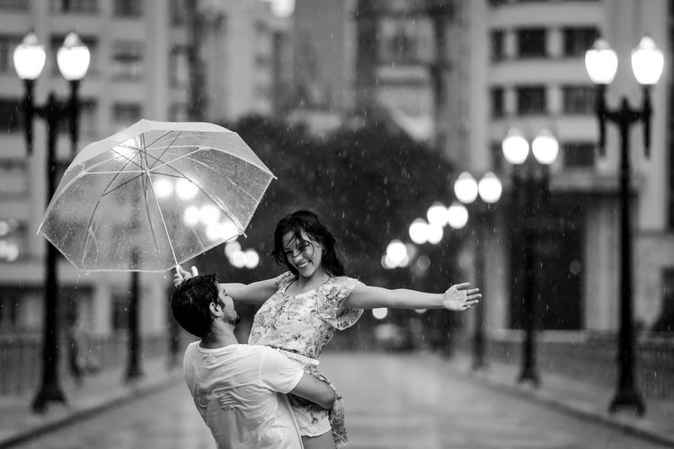 Woman holding umbrella on street in city