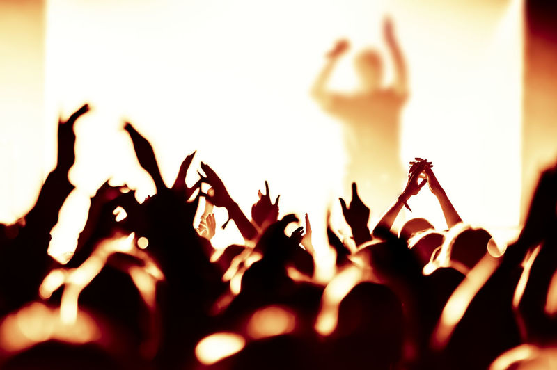Close-up of hands of people at music concert