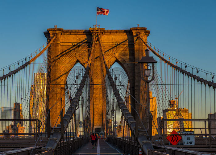 Architecture Bridge - Man Made Structure Brooklyn Bridge / New York Built Structure Chain Bridge City Clear Sky Connection Day Early Morning Flag Low Angle View Neighborhood Map Outdoors Patriotism Sky Sunrise Suspension Bridge The Architect - 2017 EyeEm Awards Tourism Transportation Travel Travel Destinations