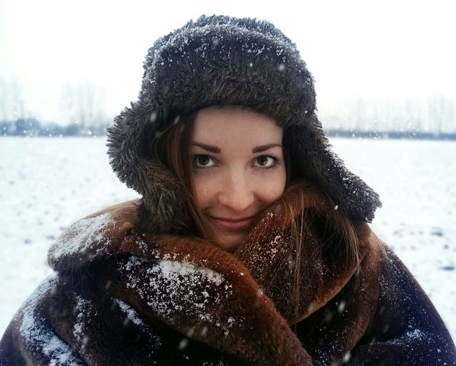 Portrait of beautiful woman wearing fur hat and sweater standing on snowy field