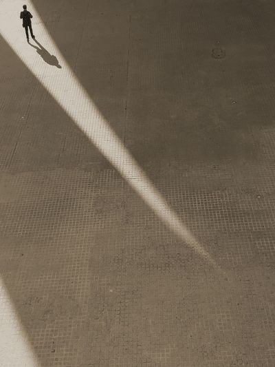 High angle view of person walking on floor during sunny day