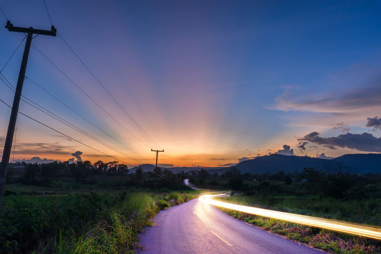 Light trail on road against sky during sunset
