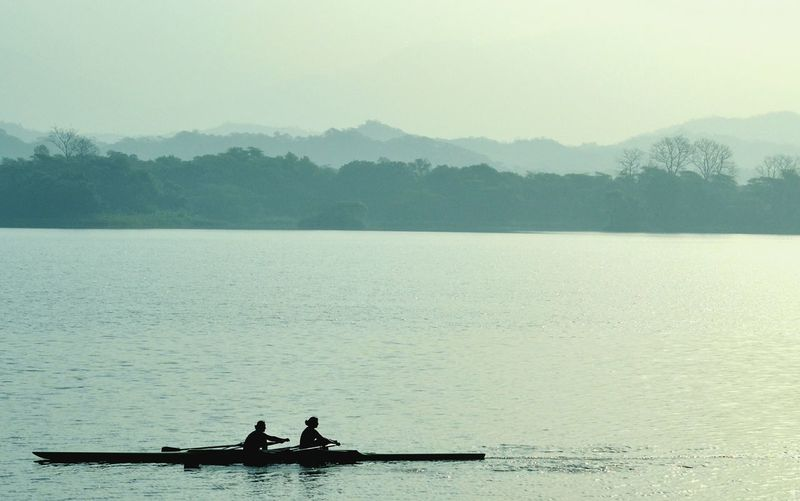 Side view of two people oaring a boat