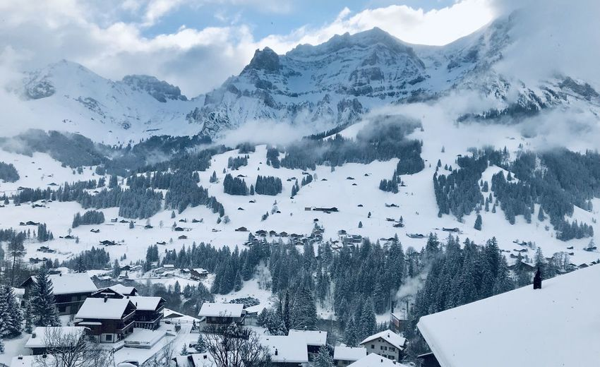 Aerial view of townscape by snow covered mountains