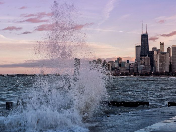 Water Splashing In Sea Against Sky At City During Sunset
