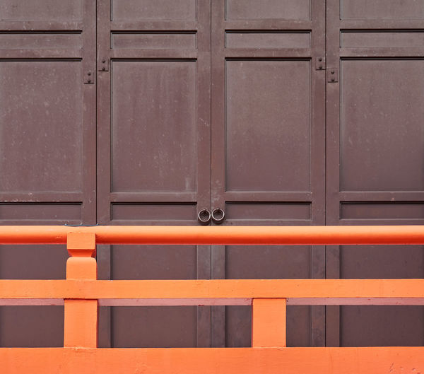 Full frame shot of closed door and railing of wooden building