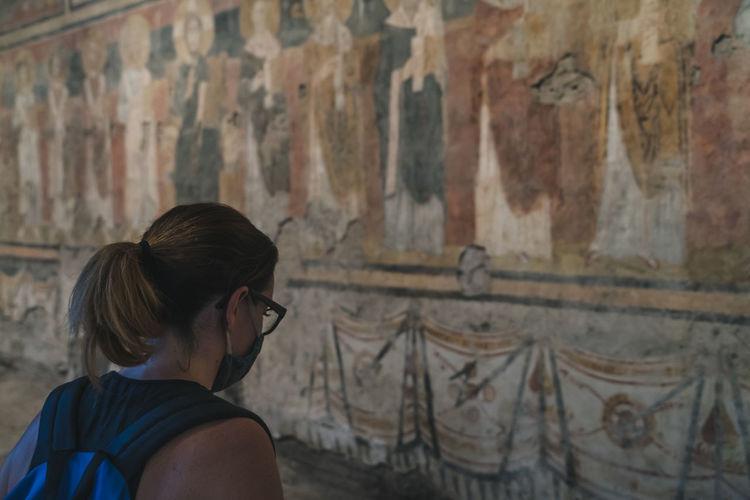 Rear view of woman looking at wall
