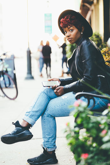 Portrait Of Young Woman Sitting On Park Bench