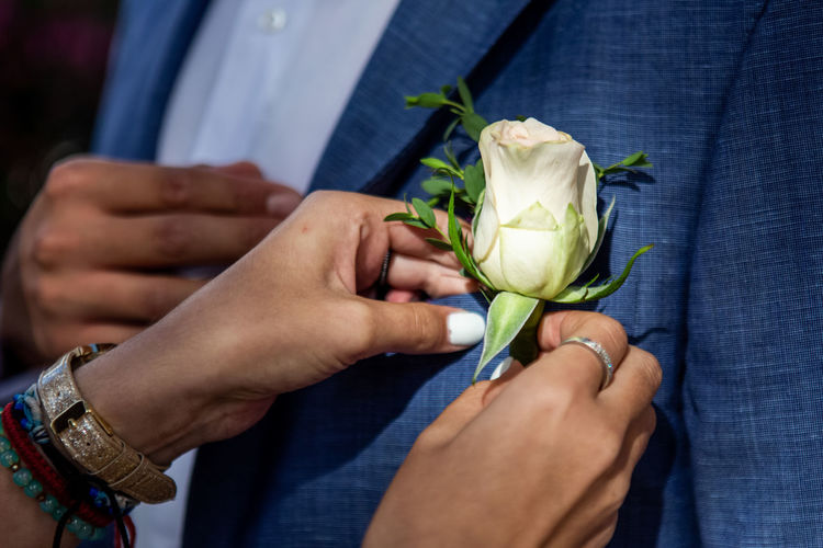 Close-up of hands attaching rose on blazer