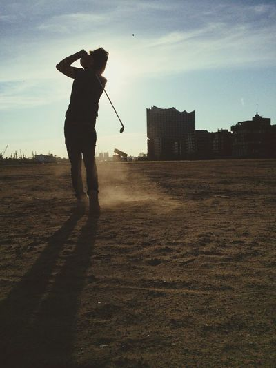 Rear view of man playing golf at dusk