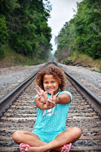 Railroad Track Railroad Track Rail Transportation Childhood Child Girls One Person Real People Females Day Offspring Sitting Looking At Camera Women Transportation Nature Hand Leisure Activity Lifestyles Plant