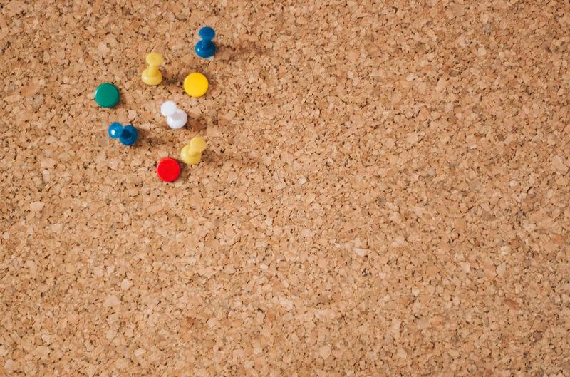 Close-up of colorful thumbtacks on board