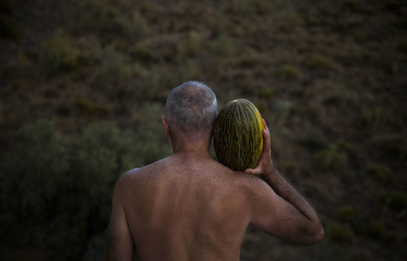 Rear view of shirtless man holding melon on shoulder in field