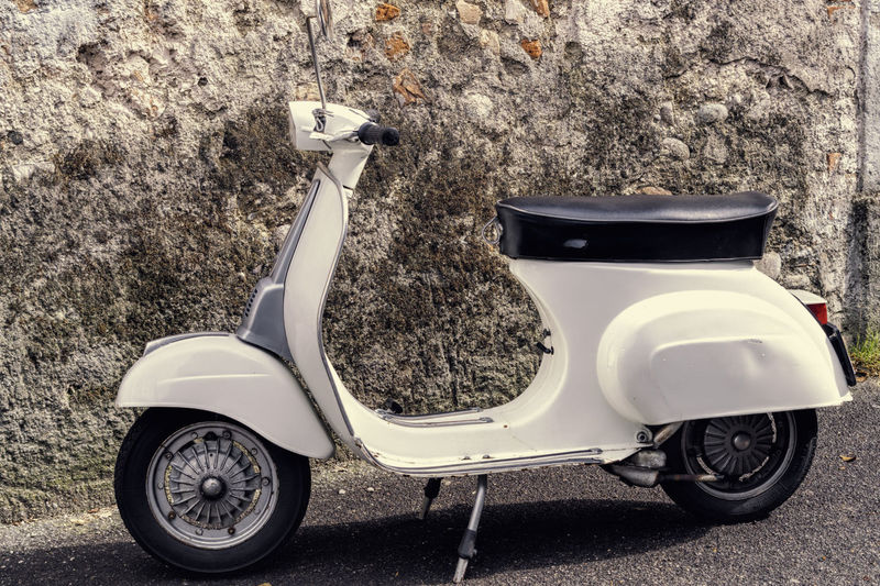 Motor scooter parked on road against wall