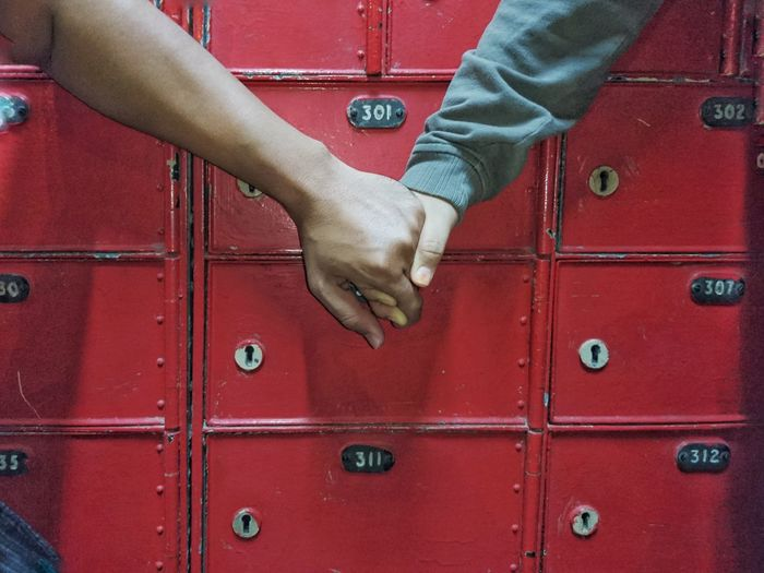 Close up of two person hand holding together in front of mailbox