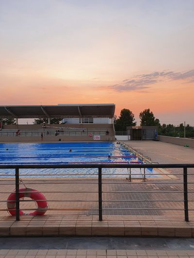 Swimming pool by building against sky during sunset