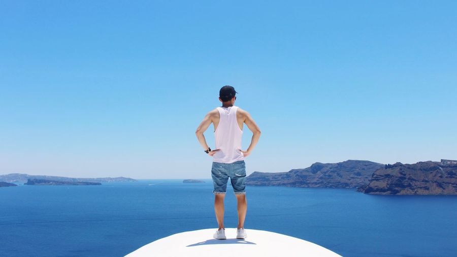 Rear view of man standing on boat in sea against clear blue sky