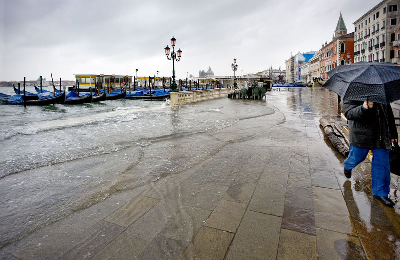 Gondolas moored at grand canal by santa maria della salute against sky