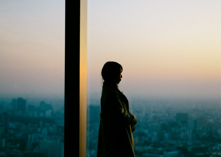 Woman standing by window during sunset