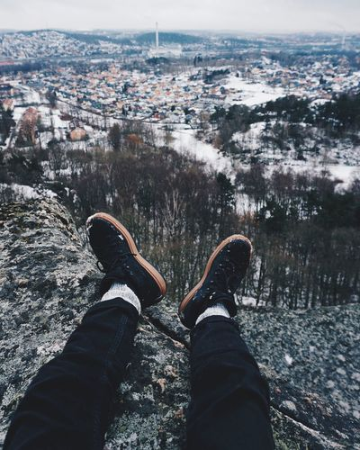 Low section of man sitting on mountain against sky during winter