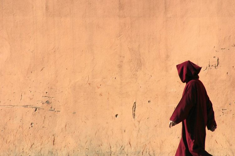 Side View Of Woman Walking By Wall