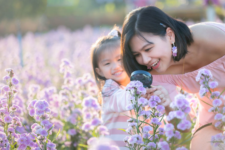 Cute girl looking through magnifying glass on flowering field with mother