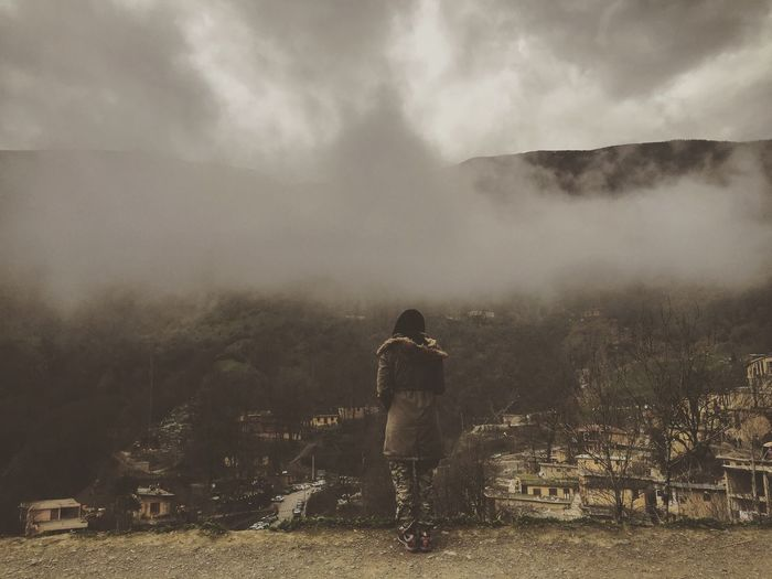 Woman Standing On Landscape Against Cloudy Sky