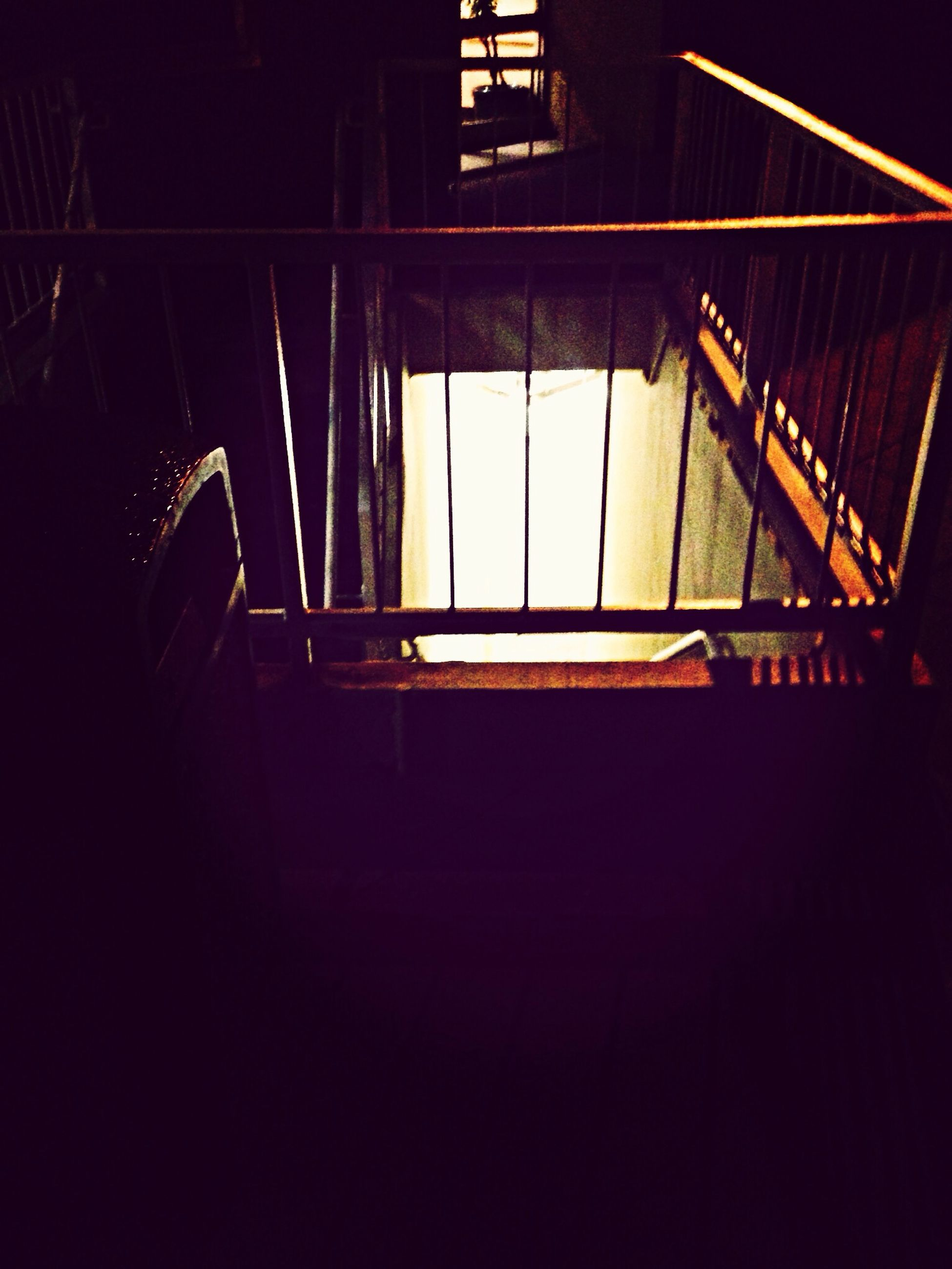 indoors, railing, staircase, steps, steps and staircases, built structure, architecture, low angle view, night, dark, sunlight, empty, absence, illuminated, shadow, metal, no people, high angle view, transportation, building