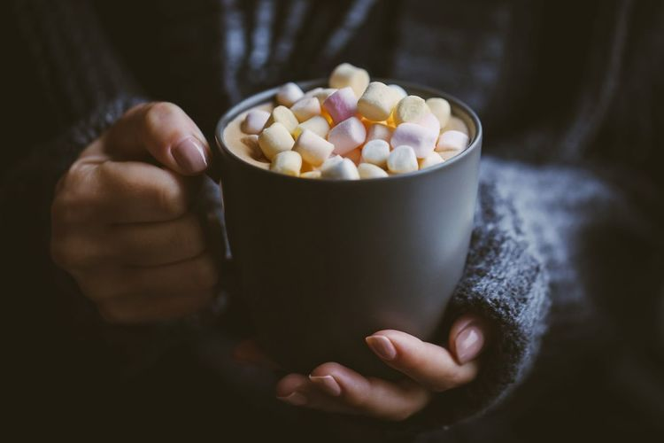 Cropped hands of woman holding marshmallows in coffee cup