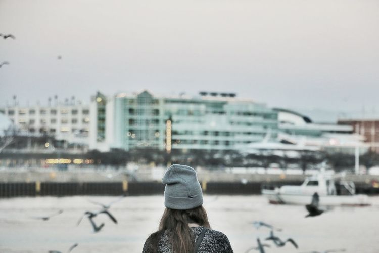 Rear View Of Woman Wearing Knit Hat Against Buildings In City