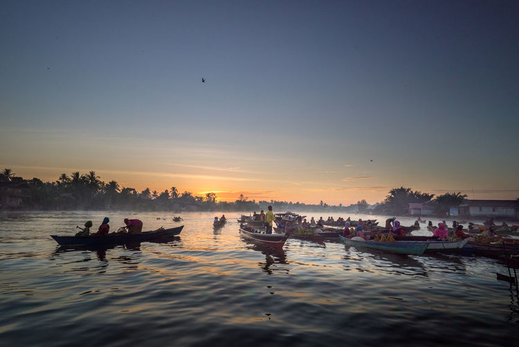 People in boats on river against sky during sunset