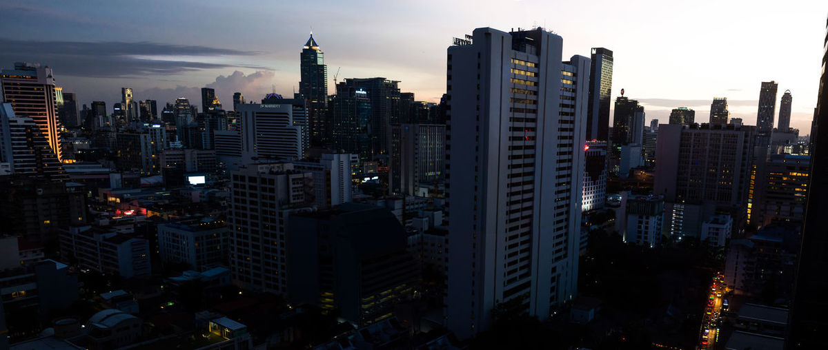 Aerial view of illuminated buildings in city against sky