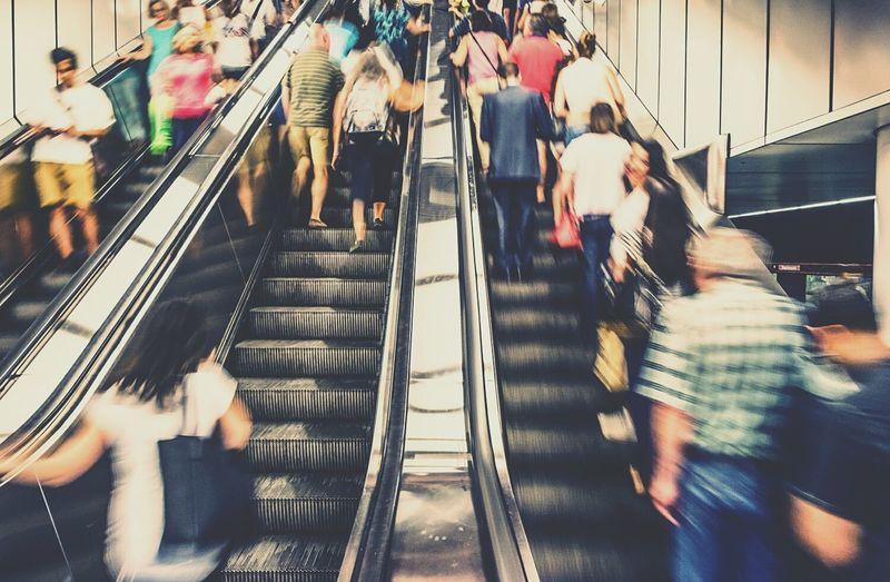 Blur image of crowd traveling on escalators