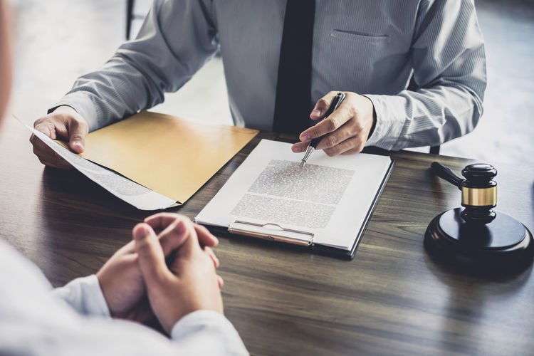 Midsection of judge writing on document while worried client sitting on table