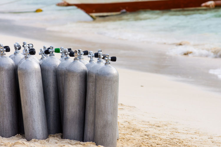 A collection of scuba divers air tanks on a tropical white sand beach. Diving Equipment Tanks Tropical Paradise White Sand Beach Beach Close-up Collection Day Diving Lesson Diving Tanks Nature No People Outdoors Oxygen Oxygen Tank Sand Scuba Diving Tank Sea Tropical Climate Water