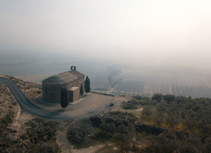High angle view of chapel on mountain against hazy sky
