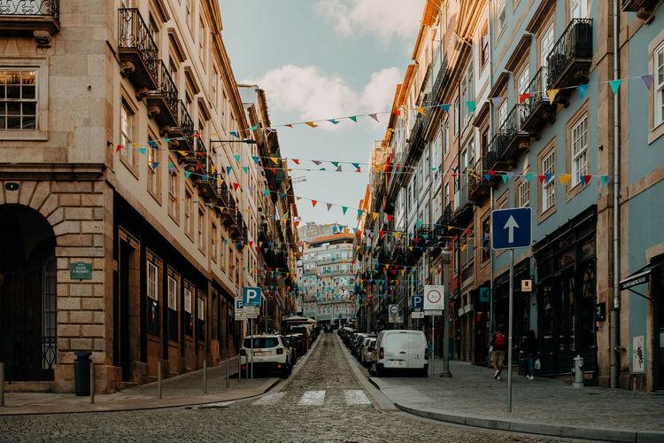 Narrow street amidst buildings in city against sky