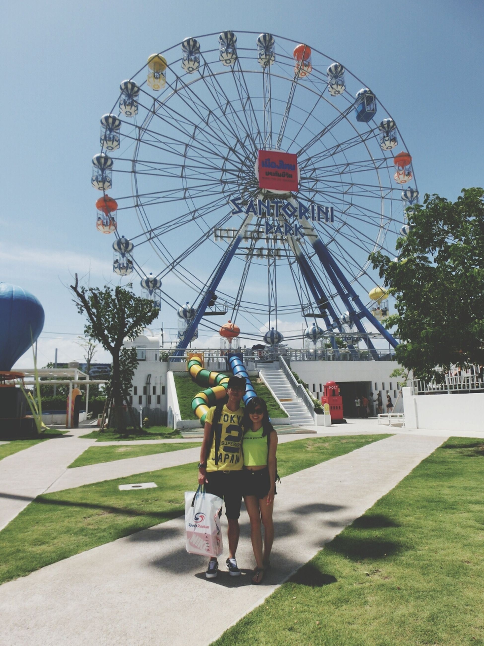 amusement park, amusement park ride, arts culture and entertainment, leisure activity, ferris wheel, lifestyles, sky, men, built structure, fun, grass, enjoyment, architecture, person, tree, park - man made space, incidental people, clear sky, day