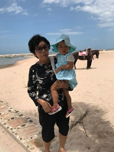 Portrait of grandmother holding granddaughter at beach against sky