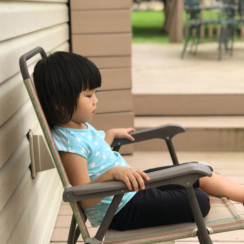 Side view of girl sitting on chair