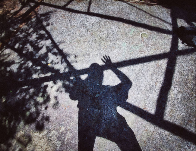 Shadow of person holding umbrella on street