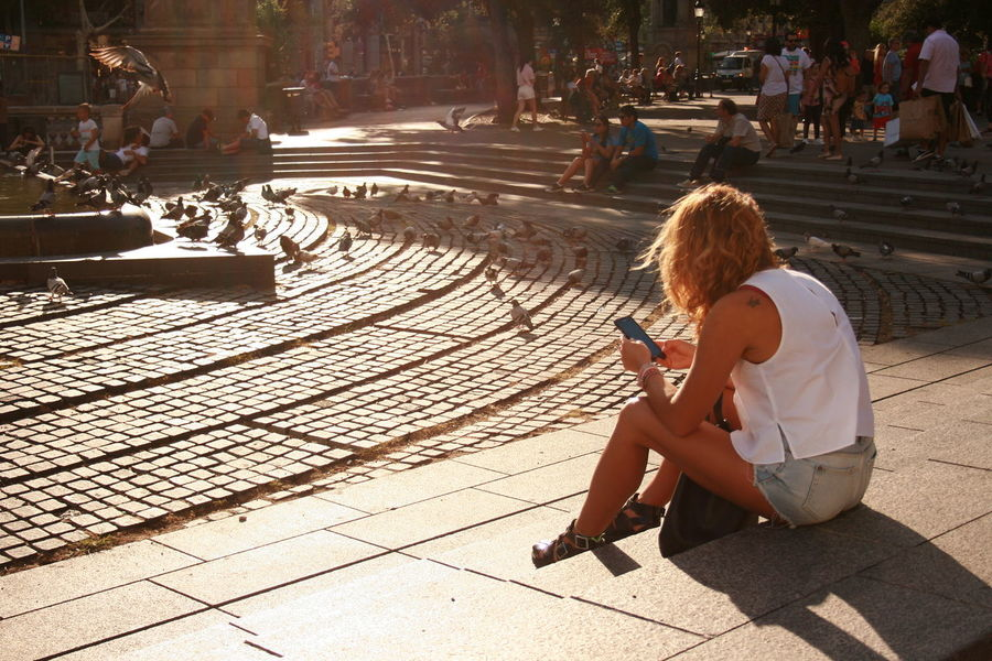 Young woman using mobile phone in summer sun light. Casual Clothing Lifestyles Mobile Phone Real People Sitting Sunlight Using Mobile Using Mobile Phone Women Young Woman