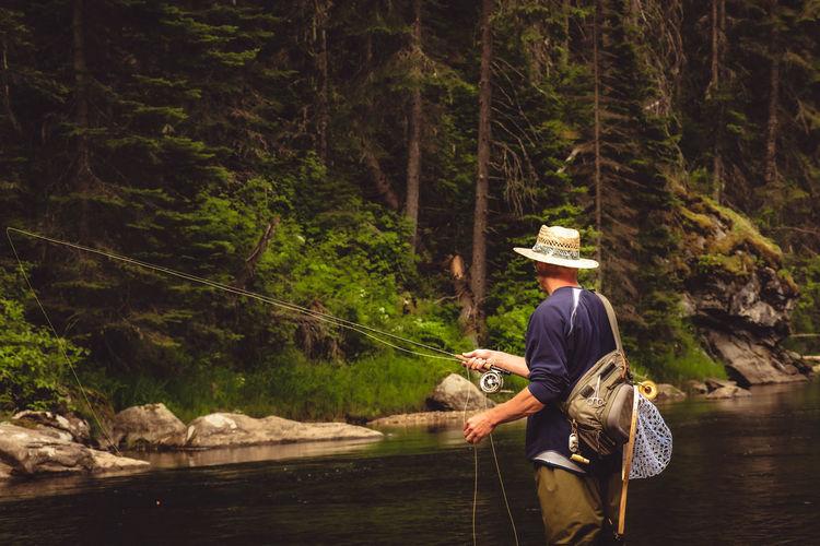 Rear view of man wearing hat fishing in river